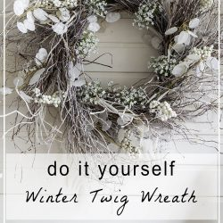 homemade twig wreath with white decorations on a winter mantel