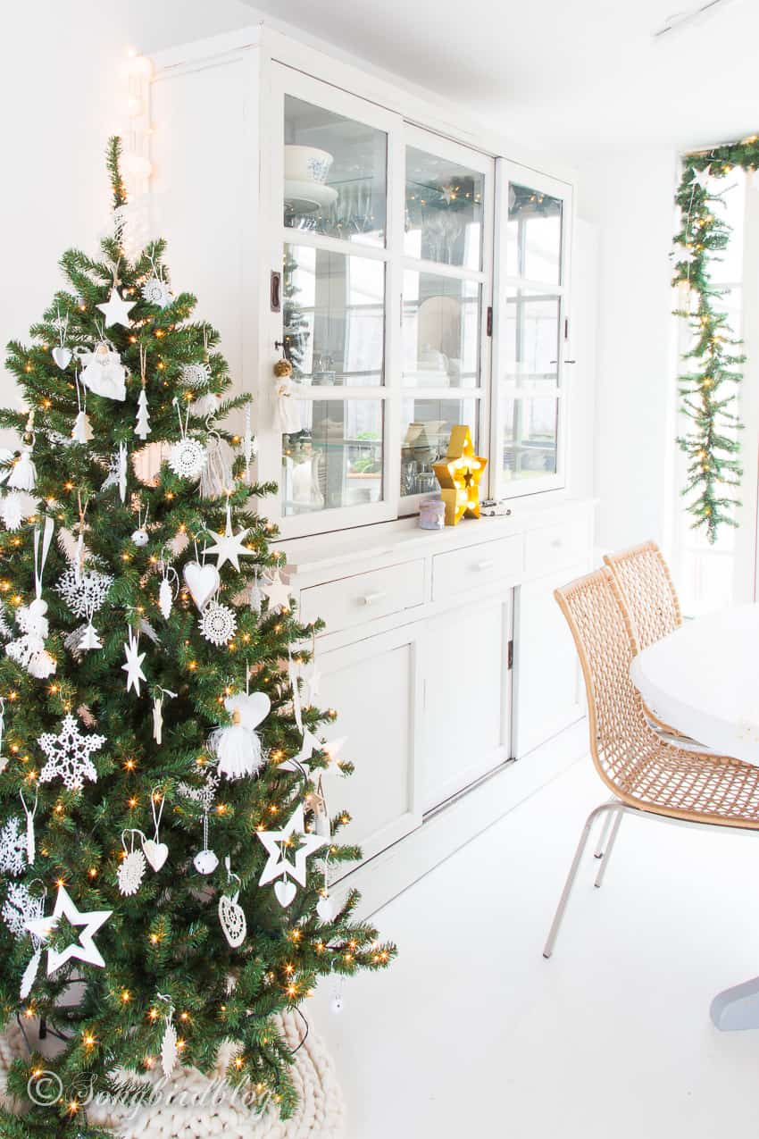 Christmas tree with white ornaments next to a white painted hutch and in front of a dining table