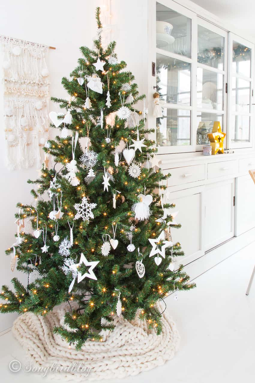 Christmas tree with white decorations in a white furnished dining room