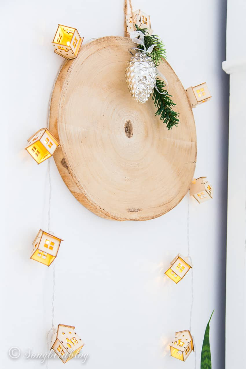 wood plaque wall decor with string lights and a Christmas ornament